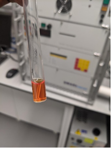 Test tube with a small amount of orange liquid in front of a cabinet in a laboratory